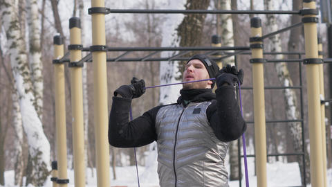 Man bodybuilder doing squat exercise on sports ground in winter park Live Action
