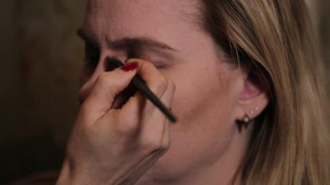 Professional make-up artist at work brush hand closeup - beauty fashion industry Footage