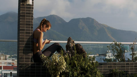 Girl Reads Sms in Phone on Terrace Watches Hills Live Action