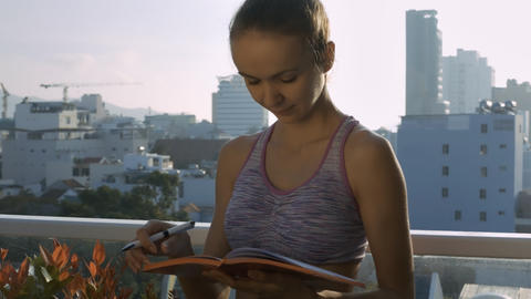 Girl Portrait Writes down Notes in Diary on Terrace Footage