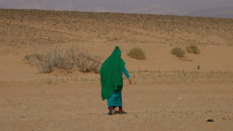 Nomad woman in traditional dress walking in desert Archivo