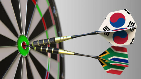 Flags of South Korea and South Africa on darts hitting bullseye of the target Live Action
