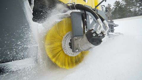 The yellow brush of snow and ice removal truck is rotating and removing snow Footage