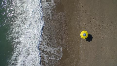 AERIAL: sunbathing on beach. No people only umbrella Photo