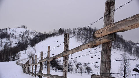 Barbed wire fence that surrounds the property lying on wooded hills and valleys  Footage