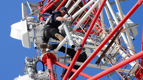 Workers working at great heights on a pole telecommunications and installs new p Footage