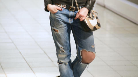 Cool Girl in Torn Jeans and Jacket against Stores Footage