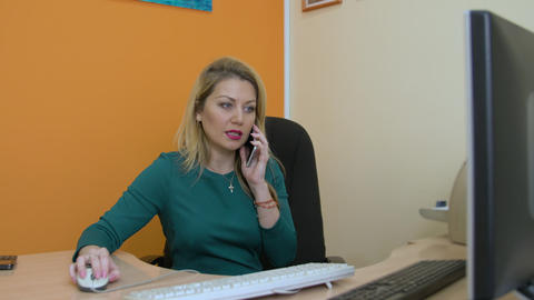 Business woman talking on cellphone and using computer in office Footage