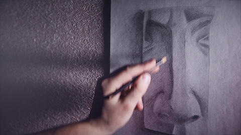 A man artist paints a plaster sketch of the nose with a graphite pencil Footage