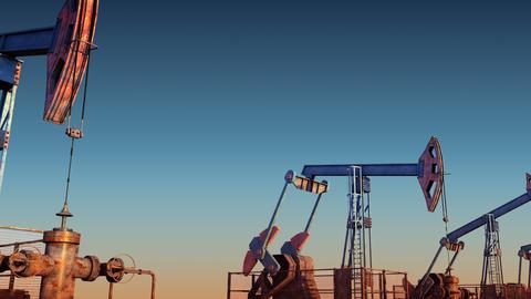 Looped move oil pump jacks against blue sunset sky Animation