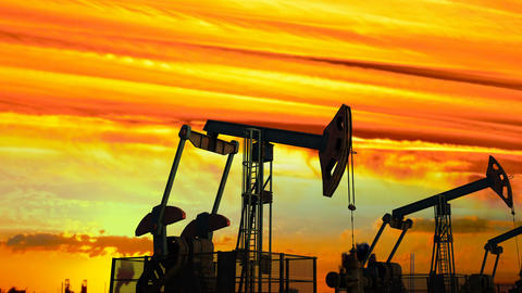 Looped move along oil pump jacks against dusk Animation