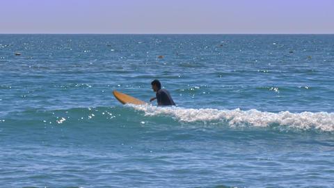 Surf Beginner Sits on Board Paddles between Waves Footage