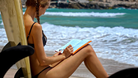 Girl Sits on Beach with Diary at Rolling Waves Footage