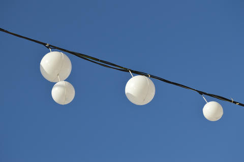 White garland balloons oscillate in the wind against blue sky and clouds Fotografía