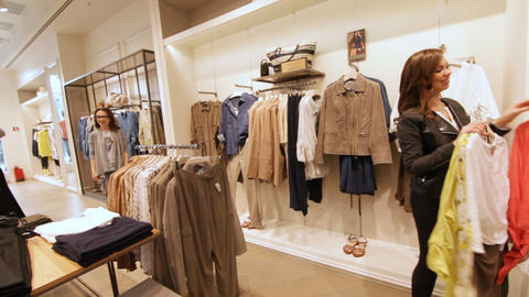 Girl Tries on Beige Jacket Shows Friends in Mall Archivo