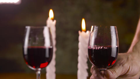 Man putting on table glass with red wine with candle light for romantic dinner Footage