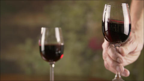 Close up man hand stirring red wine in glass before tasting slow motion Live Action