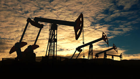 Working oil pump jacks against sunset cloudscape Footage