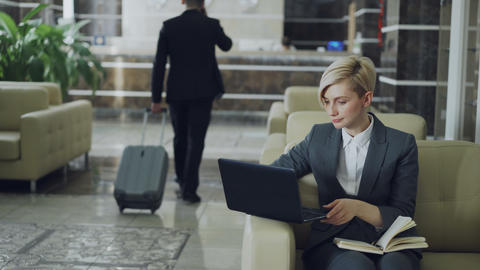 Blonde businesswoman sitting in armchair with notepad and laptop computer while Footage