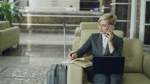 Pan shot of blonde busy businesswoman sitting in armchair in hotel lobby talking Footage