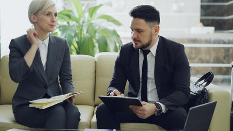 Blonde businesswoman talking to confident male colleague with clipboard at hotel Footage