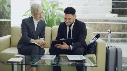 Two female and male business colleagues using digital tablet and talking at Footage