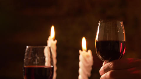 Person taking one of two glasses with red wine during romantic date Footage