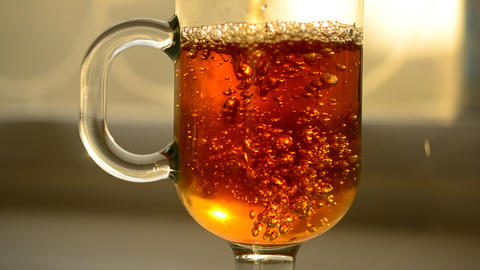 Pouring black tea into empty glass cup with bubbles and foam Footage