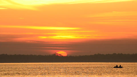 Motor boat moves on water at sunrise with sun on horizon Live Action