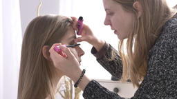 Makeup caucasian artist paints the eyes of beautiful young brunette woman close Footage