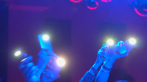 People are waving lights and mobile phones during the concert Footage