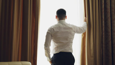 Businessman unveil curtains in hotel room at the morning and looking into window Footage