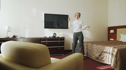 Happy businesswoman dancing and singing while listening music on wireless Live Action