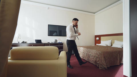 Confident businessman talking on mobile phone while walking around hotel room Footage