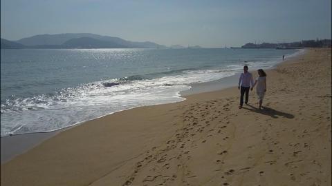 Couple Walks by Ocean Rolling Waves against Hills Footage