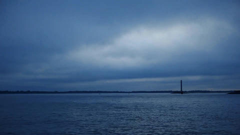 Dynamic clouds move fast over water and lighthouse Footage