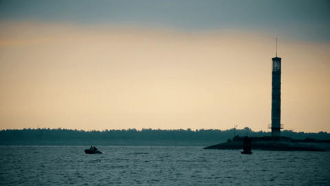 Silhouettes of two men in a boat near lighthouse at dusk Footage