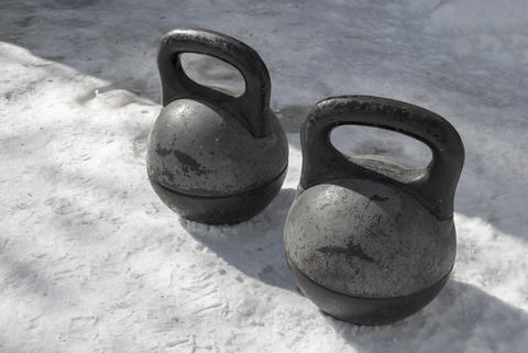 Two old black heavy kettlebell stand on the snow. Before the pra Photo