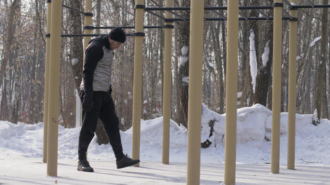 Sport man doing workout exercise on winter sports ground. Fitness man training Footage