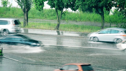 Many cars driving on road flooded with water during rain Footage