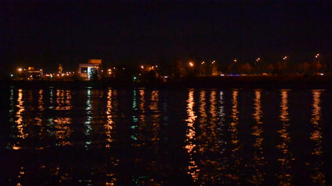 Defocused city lights over water come into focus Footage