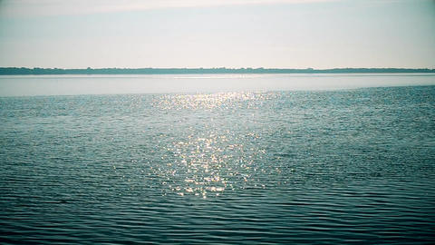 Sun shin sparkles on water surface of river or lake Filmmaterial