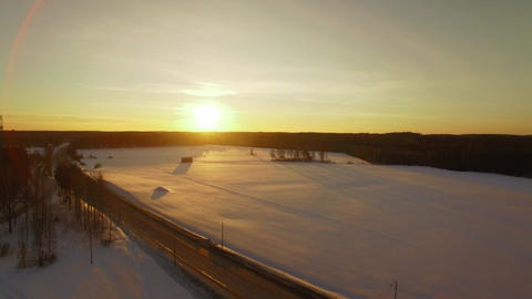 Snowy fields by a small highway during sunset Live Action