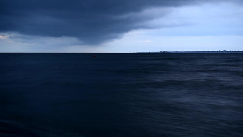 Dark blue rainy clouds move over water Footage