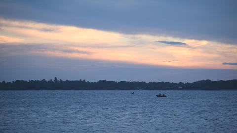 Silhouette of a moving rubber boat at dusk on river Footage