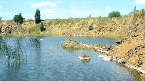 Beautiful landscape of lake in summer with basalt rocks, stones, calm water Footage