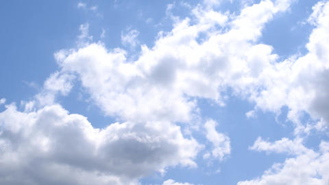 Beautiful white and grey cumulus clouds moving quickly on background of blue sky Footage