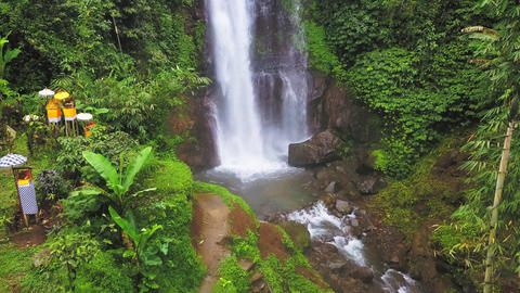 Aerial tilt up and ahead drone shot above beautiful waterfall in Bali island Footage