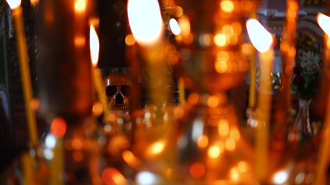 Skull in focus, in the foreground burning candles in the Christian Orthodox Footage
