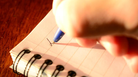 Hand writing DEAR DAD with a blue ballpoint pen in notepad Footage